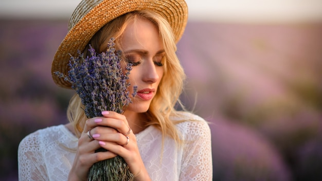 Young dreamy woman with bouquet in her hands standing in flowering lavender field