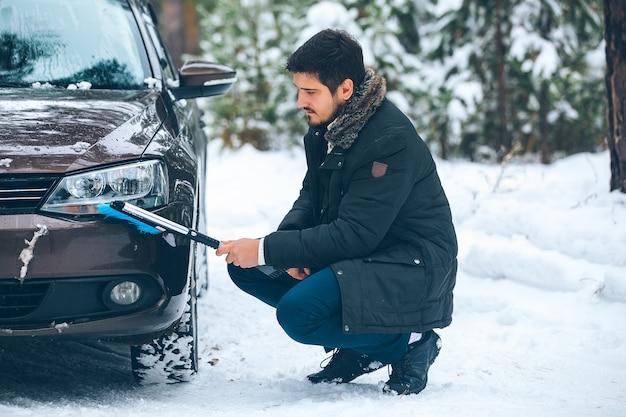 Молодой водитель мужчина зимой чистит фары автомобиля от снега