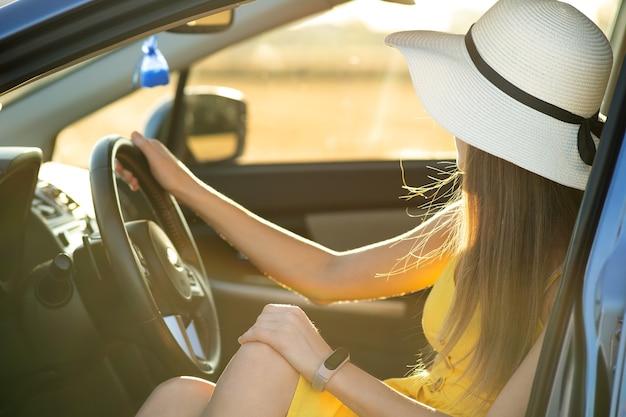 노란 드레스와 밀짚 모자를 쓴 젊은 드라이버 소녀는 차를 운전하는 운전대 뒤에 앉아 있습니다. 여름 휴가 및 여행 개념입니다.