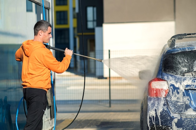 Young driver man washing his car with contactless high pressure water jet in self service car wash. Premium Photo