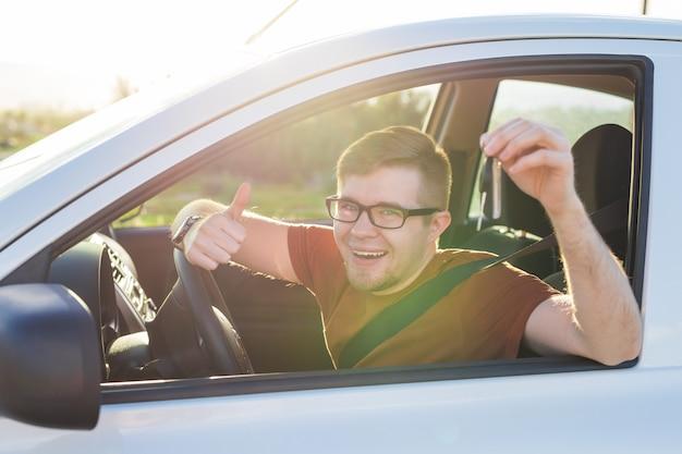 자동차 키와 엄지손가락을 보여주는 젊은 운전자가 행복합니다. 새 자동차에 대 한 자동차 키를 들고 남자입니다. 렌트카 또는 운전 면허증 개념은 남성이 도로 여행에서 아름다운 자연 속에서 운전하는 것입니다.