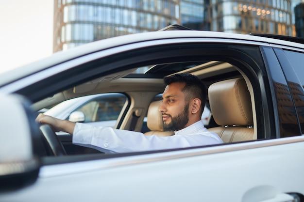 젊은 운전자가 차에 앉아 도시에서 운전