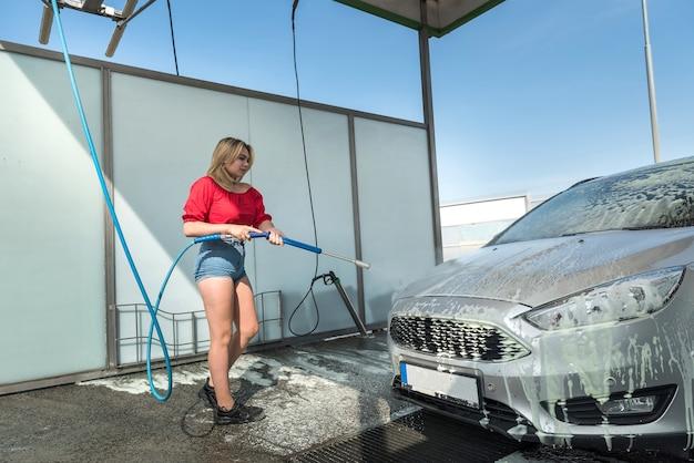 고압 호스의 젊은 운전자 여성은 수동 세차에서 먼지를 청소하기 위해 자동차에 비누 거품을 적용합니다.