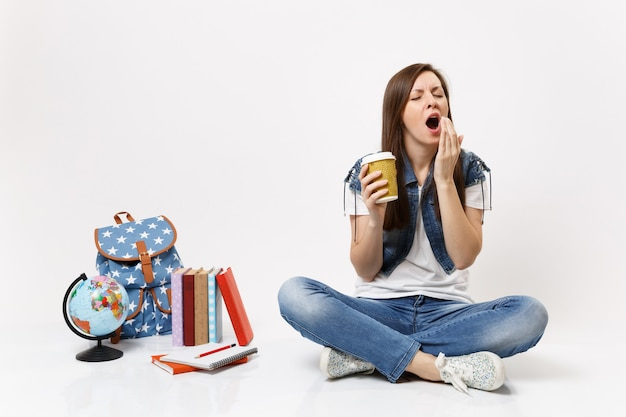 Young drowsy woman student holding paper cup with coffee or tea yawning want sleep sitting near globe, backpack, school books isolated