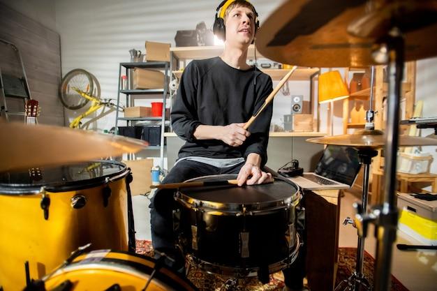 개별 리허설을하고 음악을 녹음하는 동안 심벌즈와 드럼을 두드리는 헤드폰을 가진 젊은 드러머