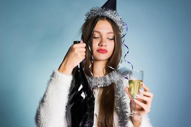 Молодая пьяная девушка с кепкой на голове празднует новый год, пьет шампанское