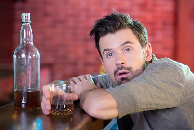 Young drunk man drinking alcohol in the bar.