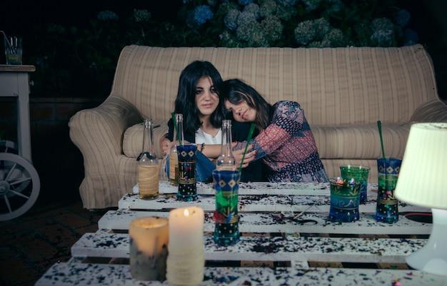 술에 취한 젊은 여성이 야외 파티 후 바닥에 앉아 있는 여자 친구와 포옹을 했습니다. 재미와 알코올 및 마약 문제 개념입니다.