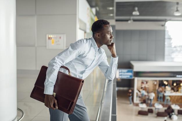 Молодой черный бизнесмен с портфелем, глядя на фуд-корт. успешный деловой человек в кафе, черный человек в формальной одежде