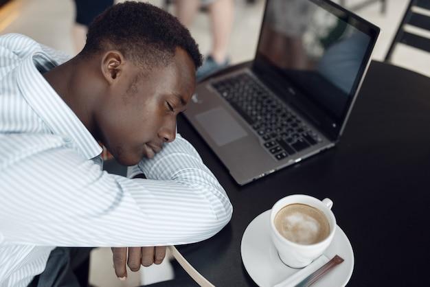 オフィスのカフェで寝ているラップトップを持つ若い黒檀の実業家。疲れたビジネスパーソンはフードコートでコーヒーを飲み、正装で黒人男性