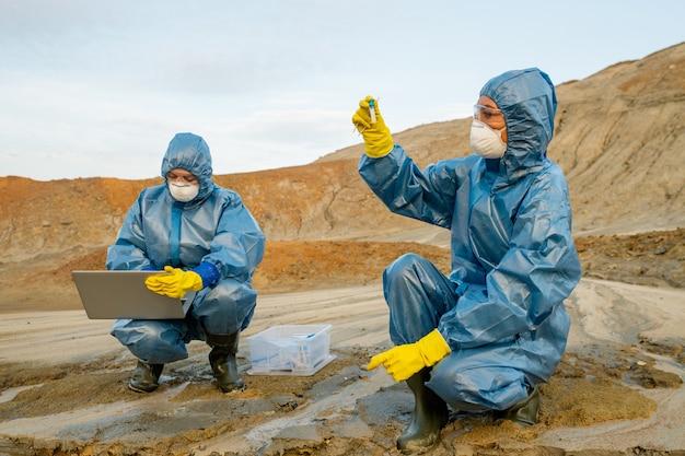 Юные экологи в резиновых перчатках и сапогах, защитных очках и респираторах изучают характеристики токсичной воды.