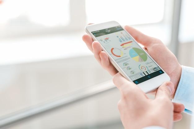 Молодой экономист или финансовый аналитик держит смартфон с диаграммами и диаграммами на экране, анализируя их