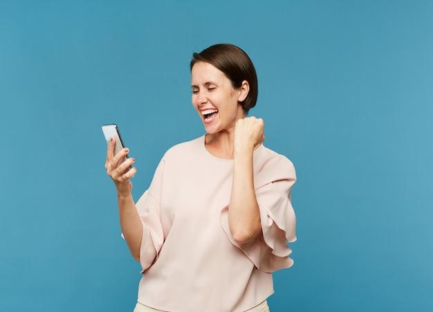 Молодая восторженная женщина смотрит на экран смартфона