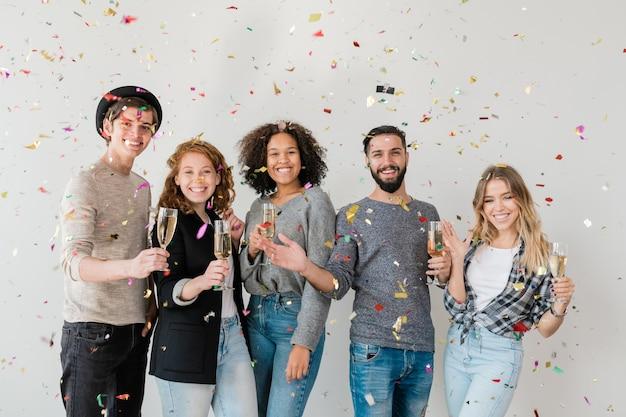 Молодые восторженные друзья из разных рас радуются шампанскому в красочных конфетти на домашней вечеринке