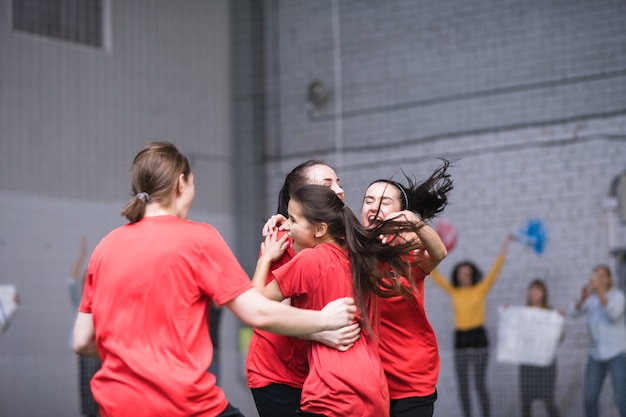 Young ecstatic sportswomen in red t-shirts embracing after successful goal during game of football