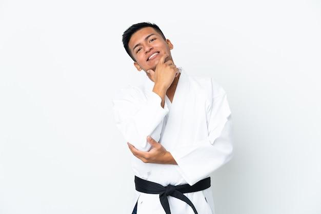 Молодой эквадорский человек занимается каратэ, изолированные на белом фоне, счастлив и улыбается