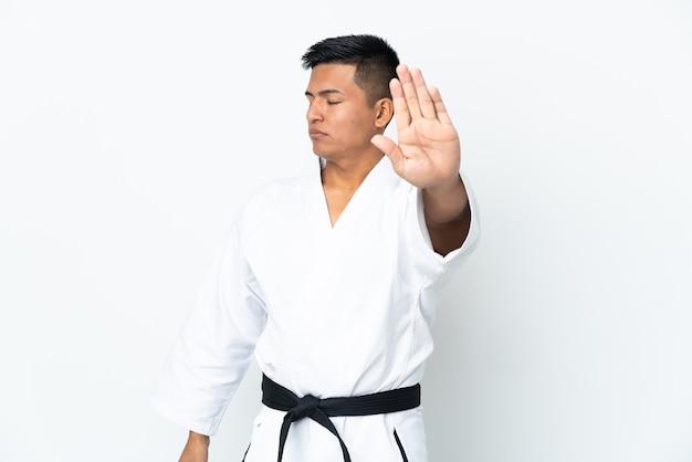 Молодой эквадорский мужчина занимается карате на белом фоне, делая жест стоп и разочарованный