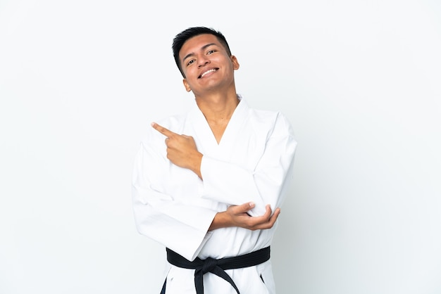 Молодой эквадорский мужчина занимается карате на белом фоне, указывая в сторону, чтобы представить продукт