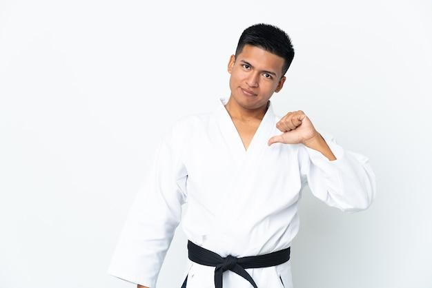 Молодой эквадорский мужчина занимается карате на белом фоне, гордый и самодовольный