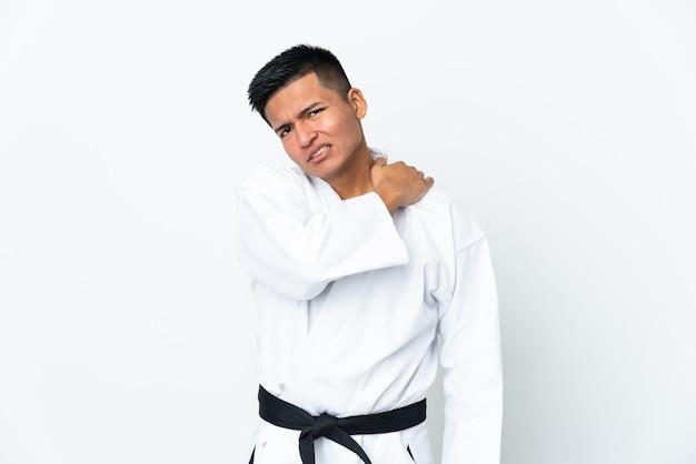 努力したために肩の痛みに苦しんでいる白で孤立した空手をやっている若いエクアドル人