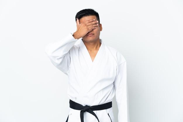 手で目を覆っている白い壁に分離された空手をやっている若いエクアドル人。何かを見たくない