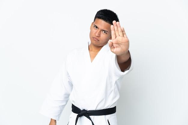 Молодой эквадорский мужчина занимается карате, изолированным на белой стене, делая стоп-жест