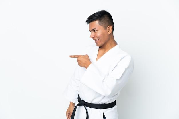 横に指を指し、製品を提示する白い壁に分離された空手をやっている若いエクアドル人男性