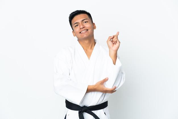 最高の兆候を示して指を持ち上げて白い壁に分離された空手をやっている若いエクアドル人