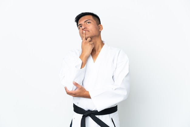 Young ecuadorian man doing karate isolated on white background having doubts while looking up