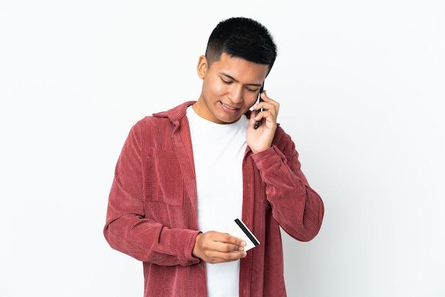 Молодой эквадорский мужчина, изолированные на белом фоне, покупает с мобильного с помощью кредитной карты