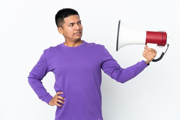 Молодой эквадорский мужчина, изолированные на белом фоне, держит мегафон с подчеркнутым выражением лица