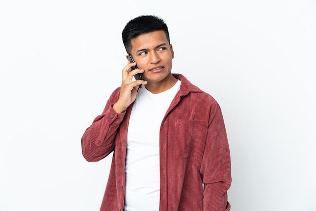 誰かと携帯電話との会話を維持している白い背景で隔離の若いエクアドル人男性
