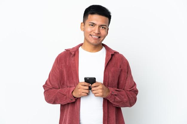Молодой эквадорский мужчина изолирован на белом фоне, глядя в камеру и улыбаясь при использовании мобильного телефона
