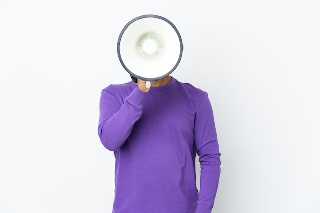뭔가를 발표하기 위해 확성기를 통해 외치는 흰색 배경에 고립 된 젊은 에콰도르 남자