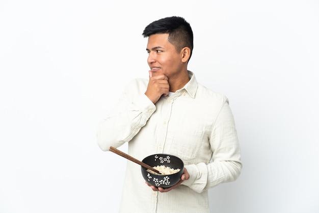 箸で麺のボウルを保持しながらアイデアを考え、側面を見て白い背景で隔離の若いエクアドル人男性