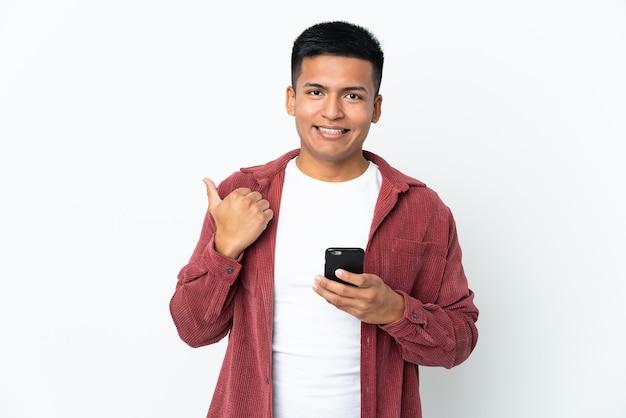 携帯電話を使用して、側面を指している白い背景で隔離の若いエクアドル人男性