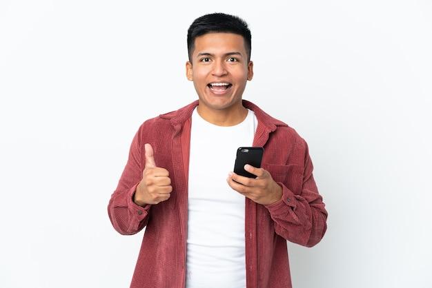 Молодой эквадорский мужчина изолирован на белом фоне, используя мобильный телефон, делая большие пальцы руки вверх
