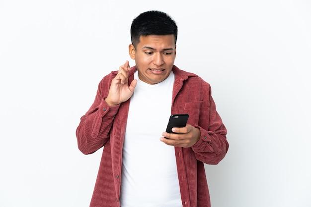 Молодой эквадорский мужчина на белом фоне с помощью мобильного телефона со скрещенными пальцами
