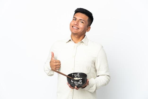 젓가락으로 국수 한 그릇을 들고 뭔가 좋은 일이 발생했기 때문에 엄지 손가락으로 흰색 배경에 고립 된 젊은 에콰도르 남자
