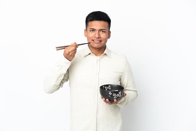 젓가락으로 국수 그릇을 들고 흰 벽에 고립 된 젊은 에콰도르 남자