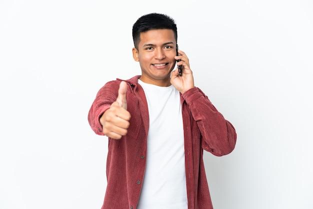 Молодой эквадорский мужчина изолирован на белой стене, разговаривает с мобильным телефоном и показывает палец вверх