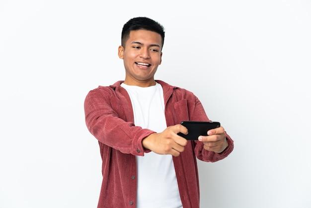 Молодой эквадорский мужчина изолирован на белой стене, играя с мобильным телефоном