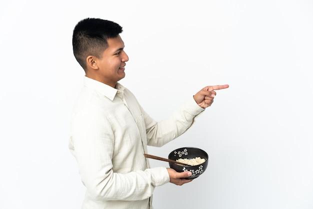 젓가락으로 국수 그릇을 들고 제품을 제시하기 위해 측면을 가리키는 흰 벽에 고립 된 젊은 에콰도르 남자
