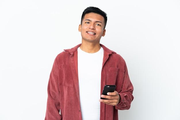 携帯電話を使用して白い壁に隔離された若いエクアドル人男性