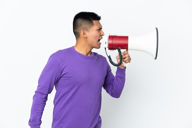 Young ecuadorian man isolated on white background shouting through a megaphone to announce something in lateral position