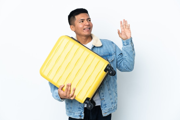 Young ecuadorian man isolated on white background in vacation with travel suitcase and saluting