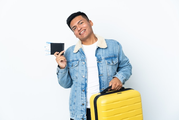 Young ecuadorian man isolated on white wall in vacation with suitcase and passport