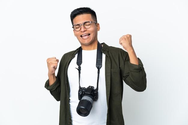 Молодой эквадорский фотограф на белом фоне празднует победу