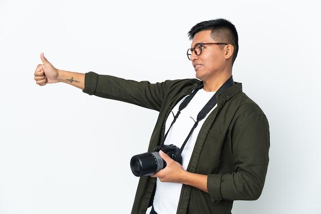 Молодой эквадорский фотограф изолирован на белом фоне, показывая большой палец вверх