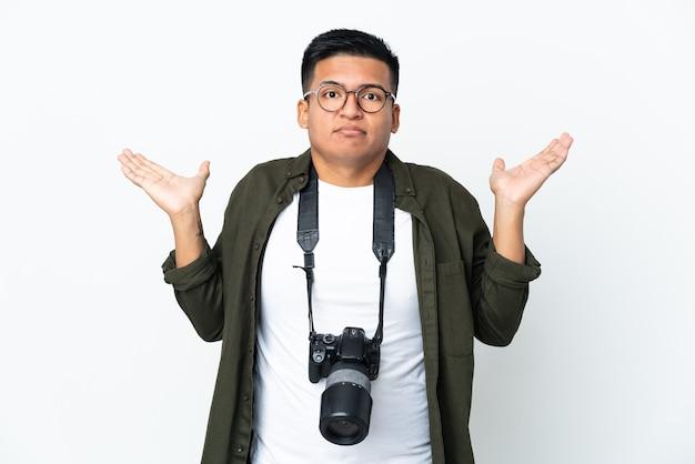 Молодой эквадорский фотограф изолирован на белом фоне, сомневаясь, поднимая руки